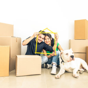 Happy couple with dog moving to a new home - Cheerful family starting a new life - Multi ethnic couple of lovers buy new apartment
